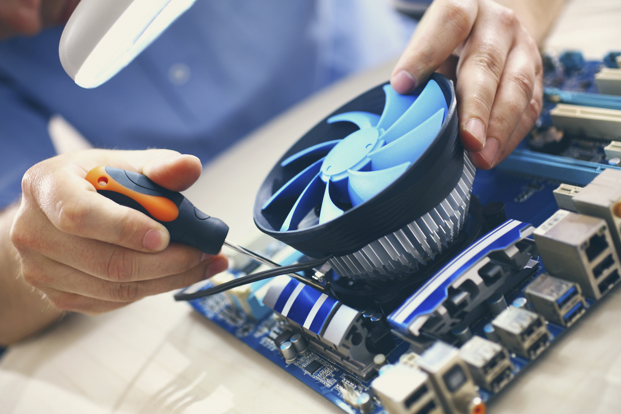 Unrecognizable adult male technician replacing CPU cooler on computer motherboard. The procedure is being done on well lit table. He's using magnifying glass with light. Wearing blue shirt with rolled back sleeves.